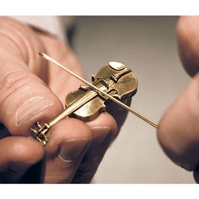 Goldschmiede sind es gewohnt, sehr fein zu arbeiten. So kam Wilhelm Hadler die Idee, eine Geige in Miniatur nachzubauen. Die Geige ist aus purem Gold und tatsächlich spielbar! © Goldschmiedemeister Wilhelm Hadler; Foto: kulturundwein.com
